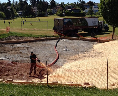 Denbow blower truck installing playground wood chips in Victoria